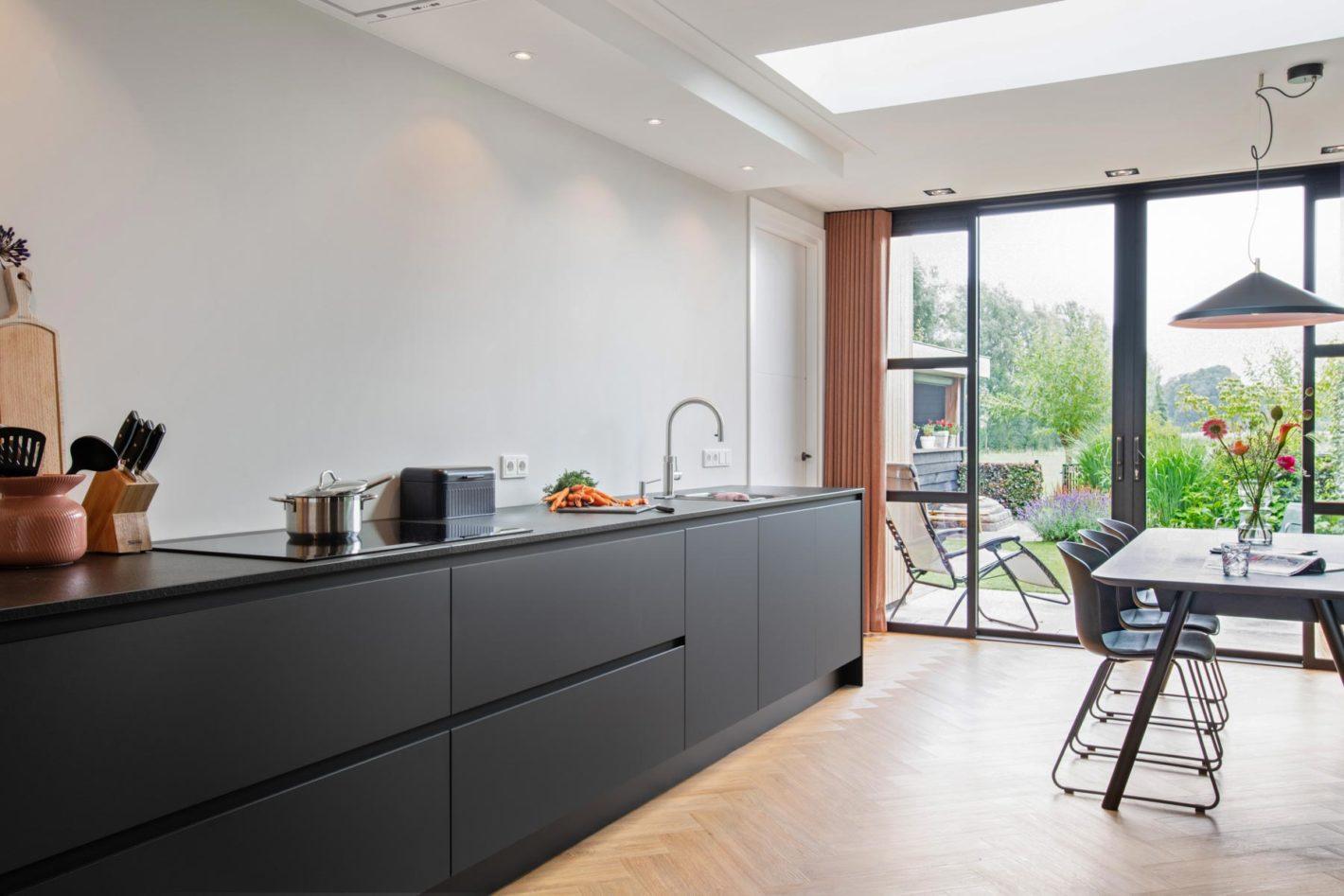 Een strakke keuken met zwart blad